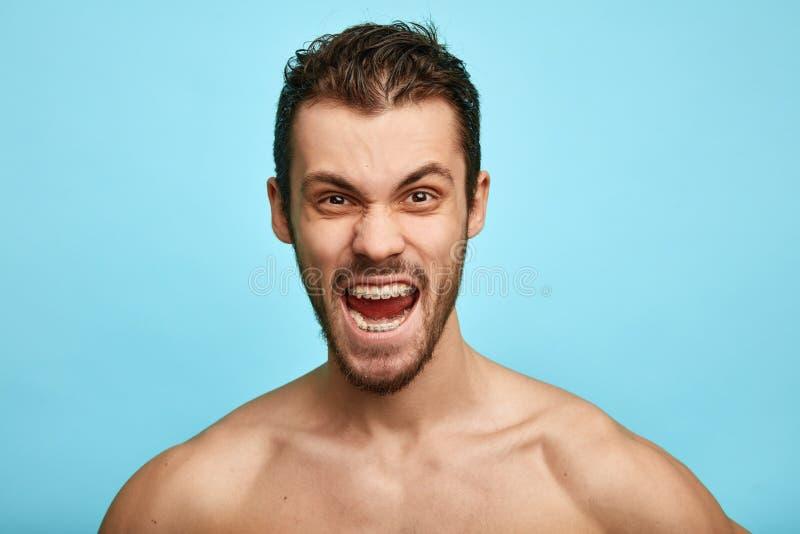 Яростный без рубашки человек показывает отрицательные эмоции, чувство, изолированное над голубой предпосылкой стоковые изображения