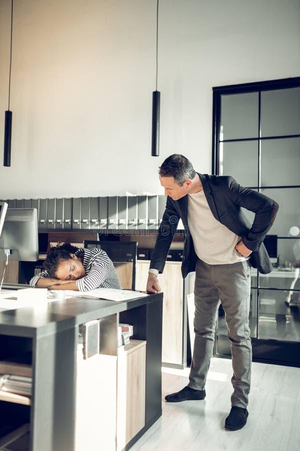 Яростный босс смотря его секретаршу спать на таблице стоковые изображения rf