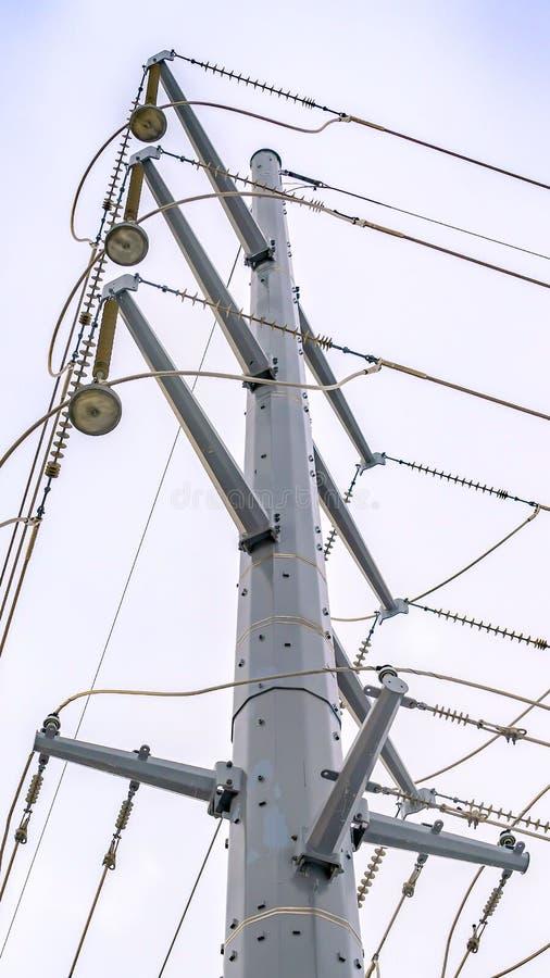 Ясная вертикаль смотря вверх на возвышаясь столбе металла поддерживая надземные линии электропередач стоковая фотография rf