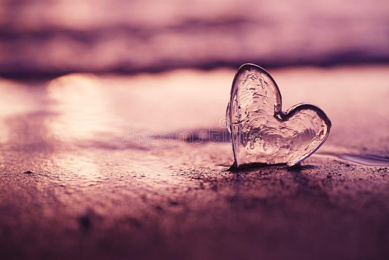 Ясное стеклянное сердце на пляже песка с светом солнца восхода солнца стоковые изображения rf
