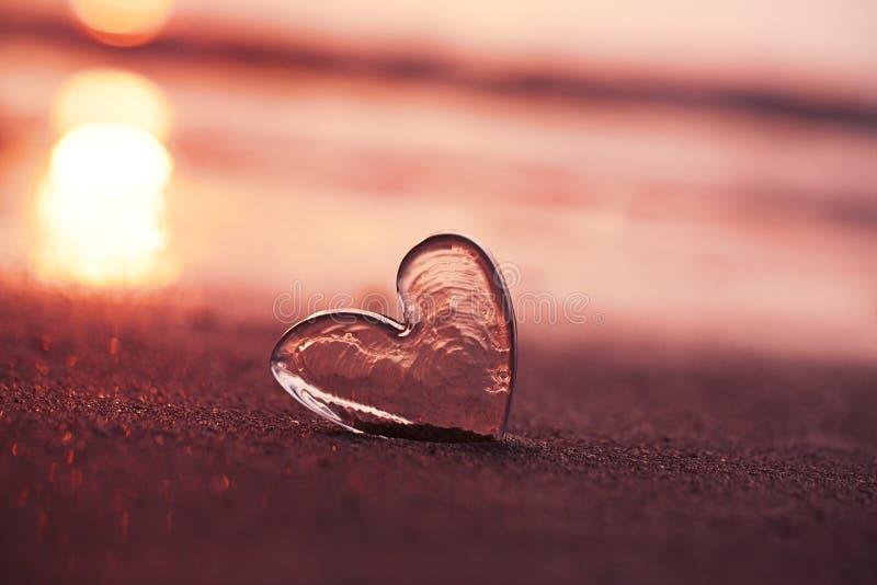 Ясное стеклянное сердце на пляже песка с светом солнца восхода солнца стоковые изображения