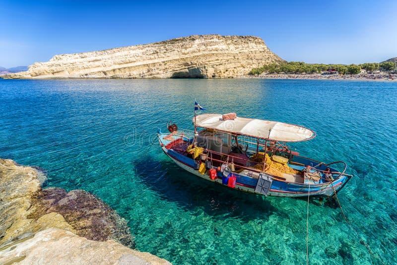 Ясные море и шлюпка на курорте Matala Крит Греция стоковые фотографии rf