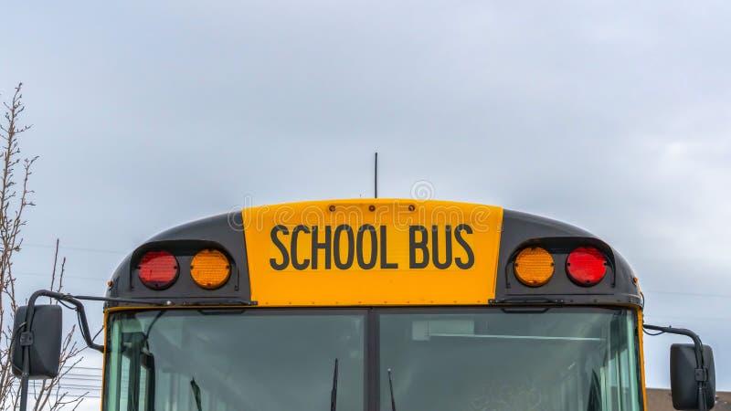 Ясный вид спереди панорамы желтого школьного автобуса с домами и облачным небом на заднем плане стоковые изображения