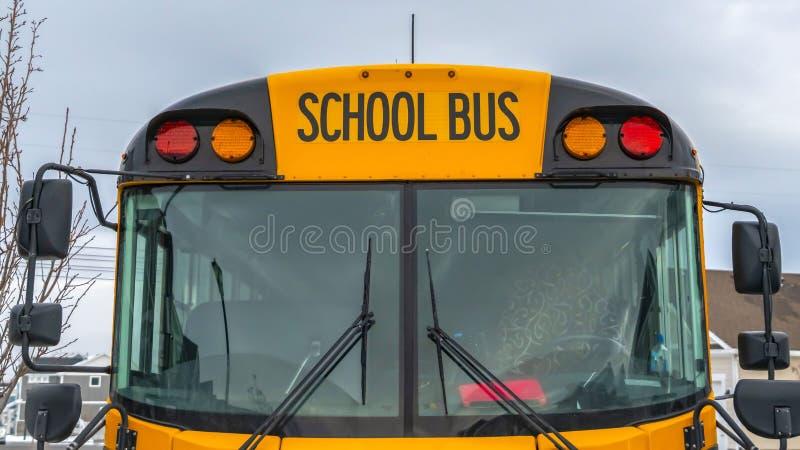 Ясный вид спереди панорамы желтого школьного автобуса с домами и облачным небом на заднем плане стоковые изображения rf