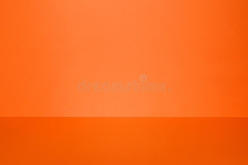 Ясный пустой оранжевый космос студии Стена и пол с светлым пятном стоковая фотография rf