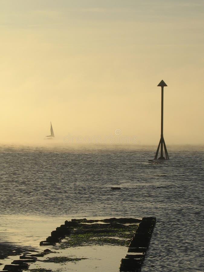 Яхта вытекая от тумана моря стоковое изображение rf