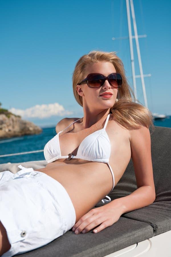 яхта женщины бикини белокурая роскошная sunbathing стоковая фотография rf