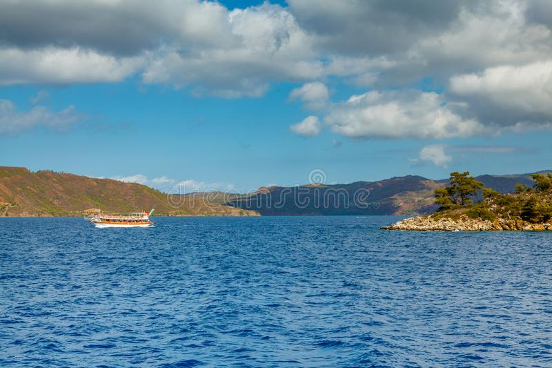 Яхта плавает близрасположенное скалистое побережье с деревьями в Aegea стоковое фото
