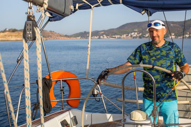 Яхта плавания шлюпки кормил шкипера человека на Эгейском море Спорт стоковая фотография