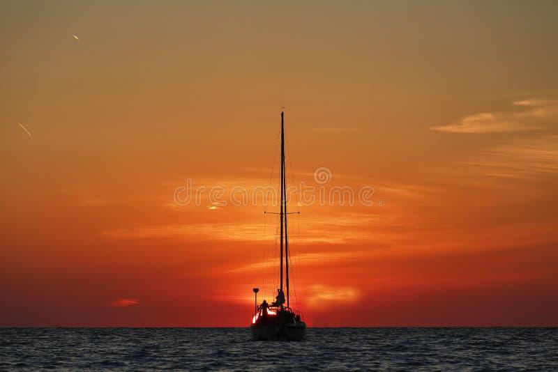 Яхта silhouetted на красивом заходе солнца стоковое изображение rf