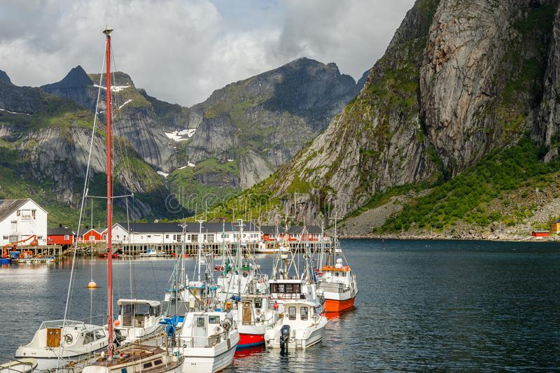 Яхты и шлюпки с горами на заднем плане на пристани в Reine, Moskenesoya, островах Lototen, графство Nordland, Норвегия стоковые изображения
