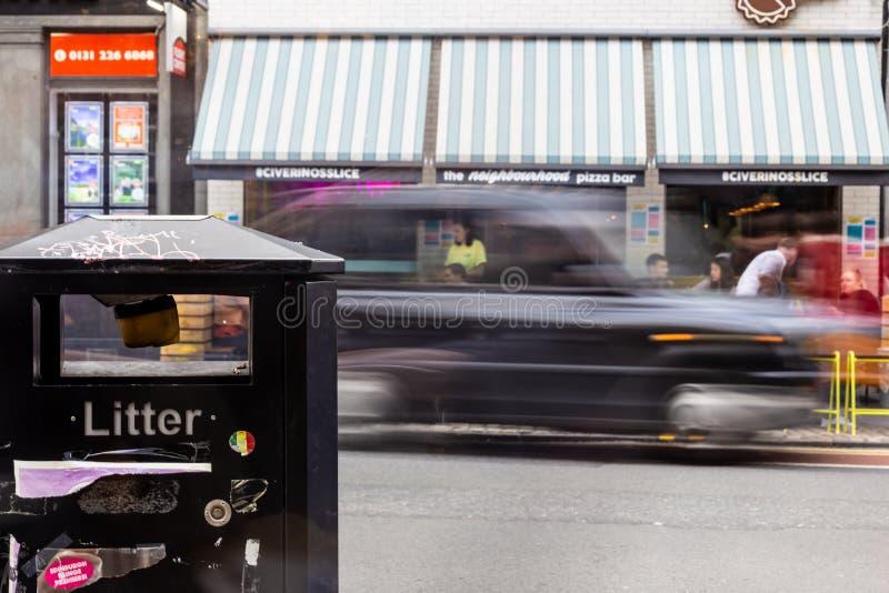 Ящик сора в переднем плане при черная кабина проходя мимо позади стоковое фото