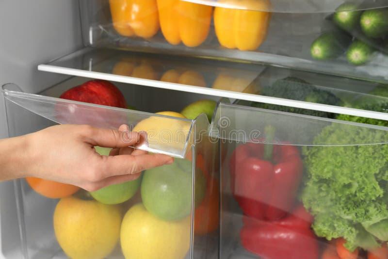 Ящик холодильника отверстия женщины со свежими фруктами стоковые фото