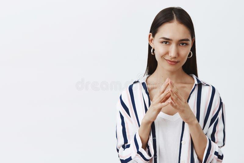 Я имею большой злий план Симпатичная уверенно и каверзная женщина в striped блузке, держа пальцы совместно и ухмыляться стоковые изображения rf