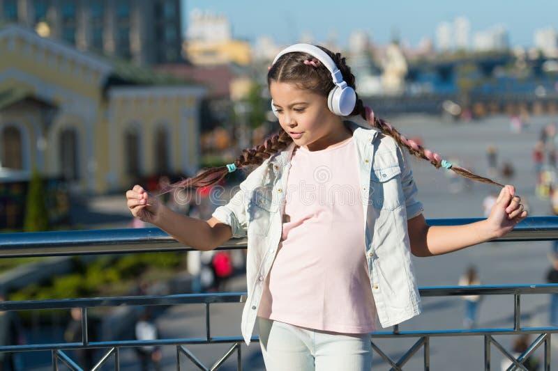 Я люблю мой стиль причесок отрезка провода Небольшой ребенок нося заплетенный стиль причесок и наушники на открытом воздухе Мален стоковое фото