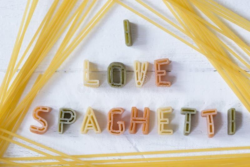 Я люблю текст спагетти написанный со шрифтом писем макаронных изделий на белой деревянной предпосылке стоковые изображения