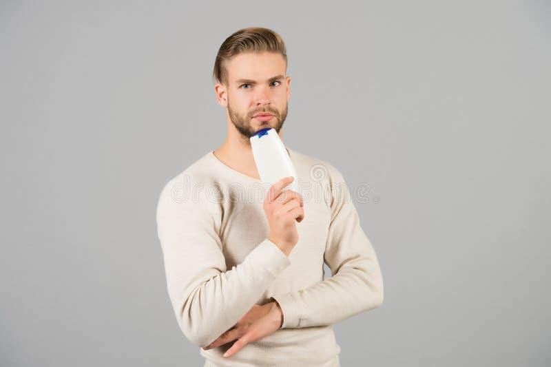Я люблю этот шампунь Стиль причёсок человека стильный держит предпосылку серого цвета продукта шампуня бутылки гигиеническую Само стоковые изображения