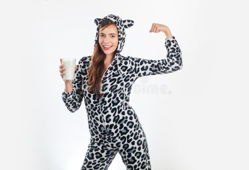 Я получил молоко смотря к партии Милая девушка в запятнанном костюме дизайна коровы держа стекло еды молокозавода Молодая женщина стоковая фотография