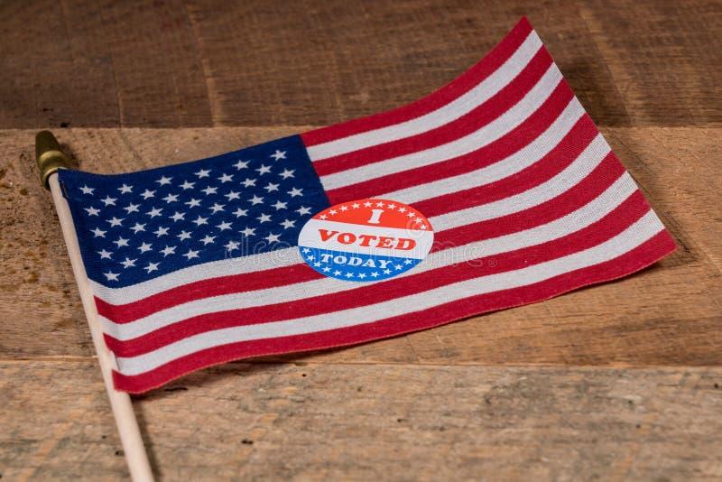 Я проголосовал сегодня бумажный стикер на флаге США и сельском деревянном столе стоковое фото