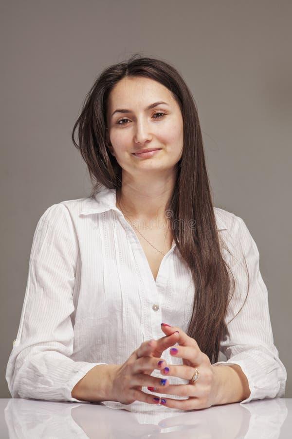 Я счастлив потому что я имею мою работу мечты! Портрет молодой красивой усмехаясь коммерсантки в офисе на рабочем месте стоковая фотография