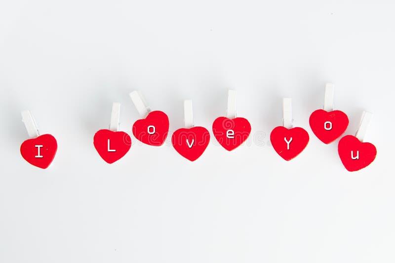 Я тебя люблю текст на зажимках для белья сердца форменных: Жулик дня ` s валентинки стоковая фотография rf