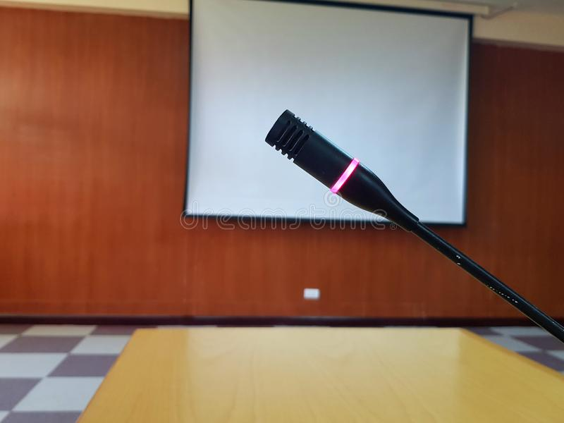 ฺBlack Microphone with red light flashing when push button on wooden desk for talking royalty free stock photography