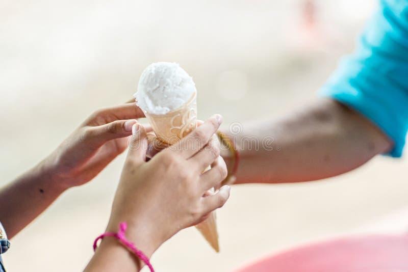 ็ руки дают детям мороженое Поделитесь конусом с детьми, которые едят мороженое Фото: Счастье только реально, когда s стоковое изображение