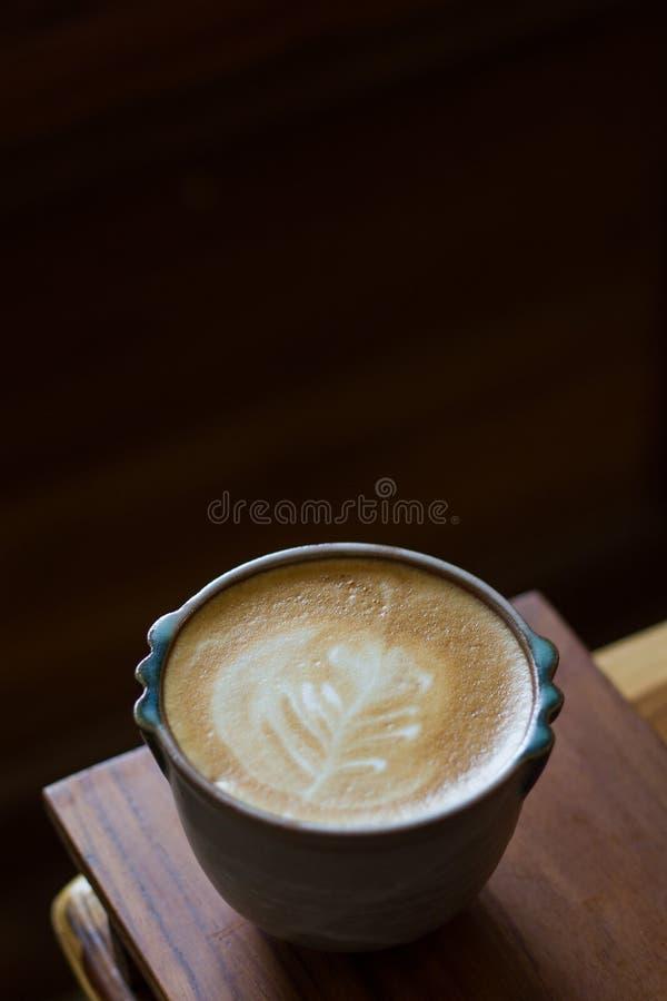 ็Hot latte art coffee on wooden table. A Cup of hot latte art coffee on wooden table royalty free stock image