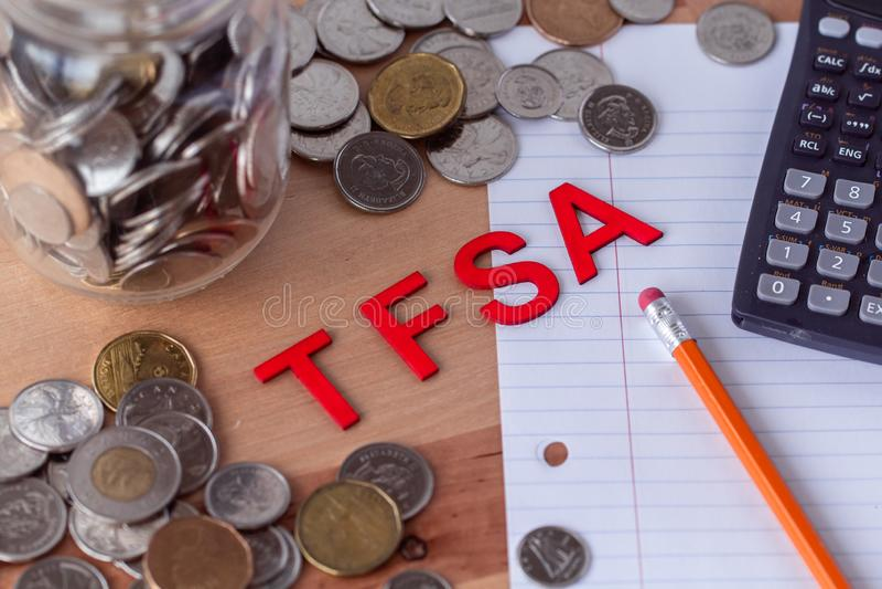 '与硬币的TFSA'免税储蓄账户标志在背景中 免版税库存照片