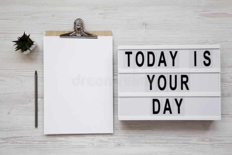 '今天是您的天'在一个现代板,有空白的纸片的剪贴板白色木表面上的,顶视图 在头顶上,从 图库摄影