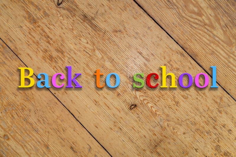 '回到在木背景的学校'五颜六色的文本 免版税库存图片