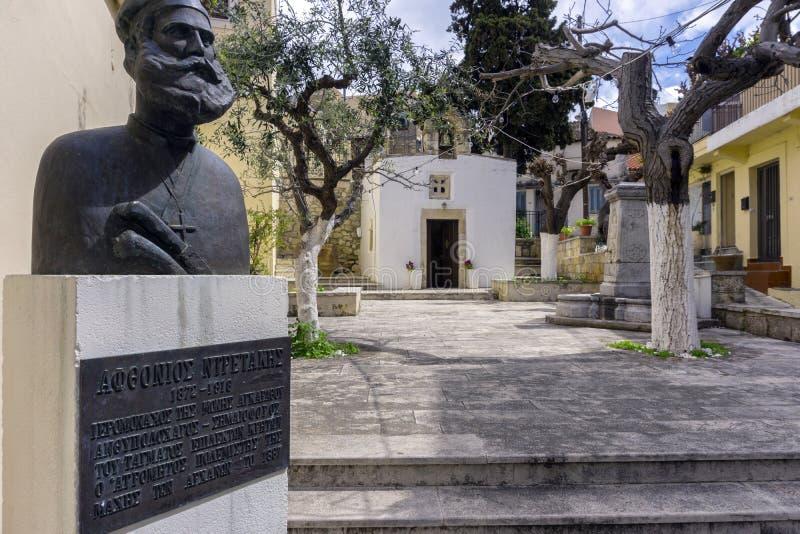'圣十字教堂'在Archanes镇 石头在庭院雕刻了喷泉,一次克里特岛革命的英雄的雕象 免版税库存照片
