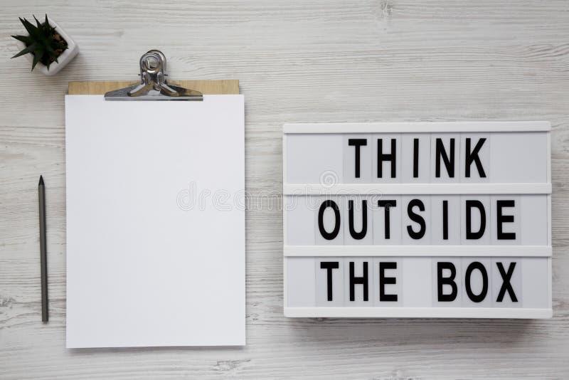 '在一个灯箱的箱子的词,有空白的纸片的剪贴板之外认为在白色木表面,顶视图的 r 免版税库存图片