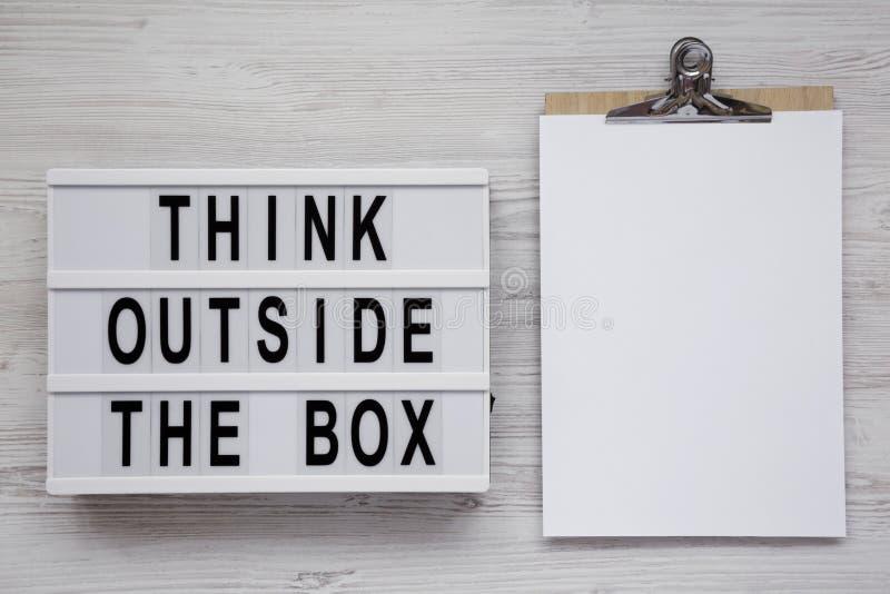'在 lightbox的箱子的词,有空白的纸片的剪贴板之外认为在白色木背景,顶视图的 ??la 免版税库存照片