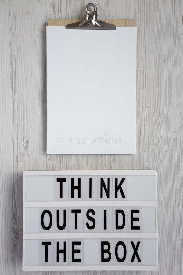 '在 lightbox的箱子的词,有空白的纸片的剪贴板之外认为白色木表面上的,顶视图 r 免版税库存图片