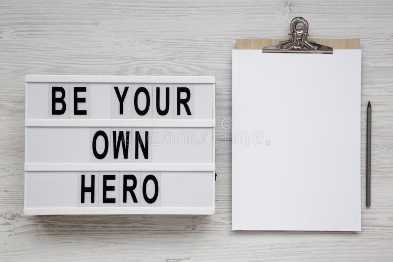 '是您在一个灯箱,有空白的纸片的剪贴板的自己的英雄'词在白色木表面,顶视图的 r 免版税库存图片