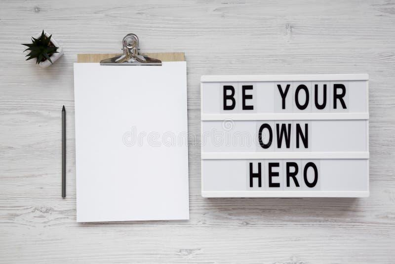 '是您在一个现代板,有空白的纸片的剪贴板的自己的英雄'词在白色木表面,顶视图的 r 图库摄影