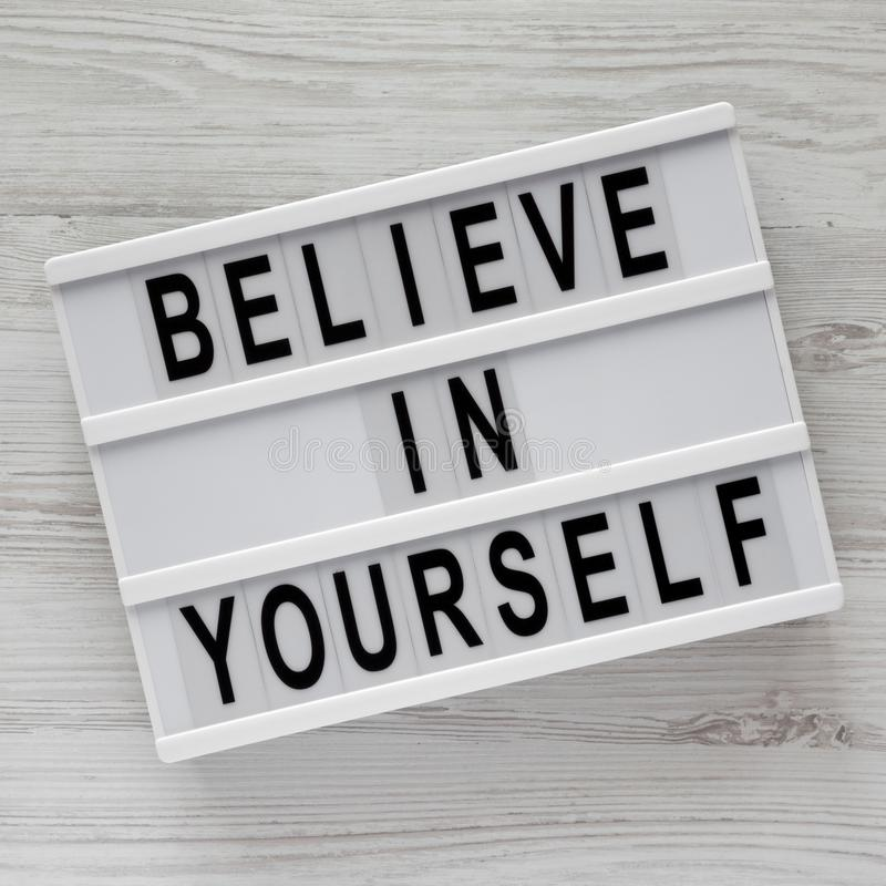 '相信你自己'在现代板白色木表面上,顶视图的词 r 免版税库存图片