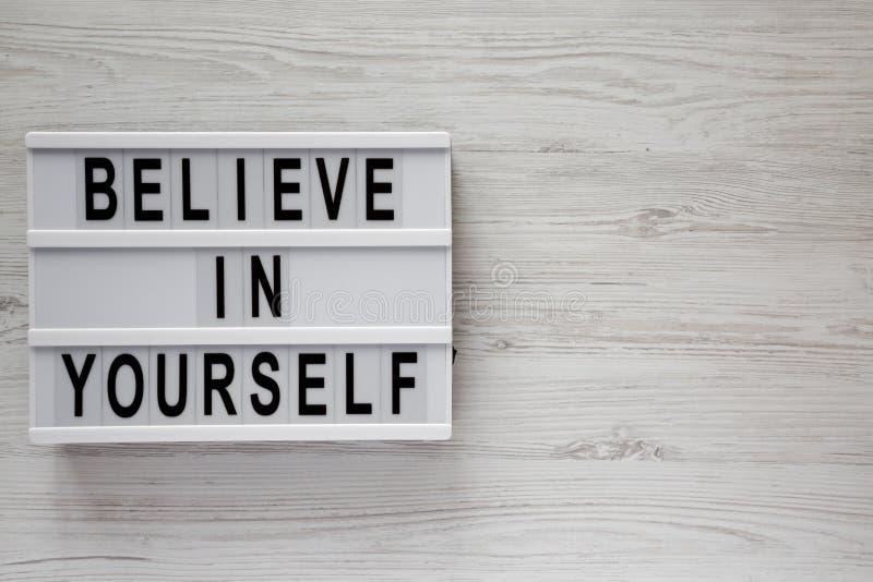 '相信你自己'在lightbox白色木表面上,顶视图的词 r r 免版税图库摄影