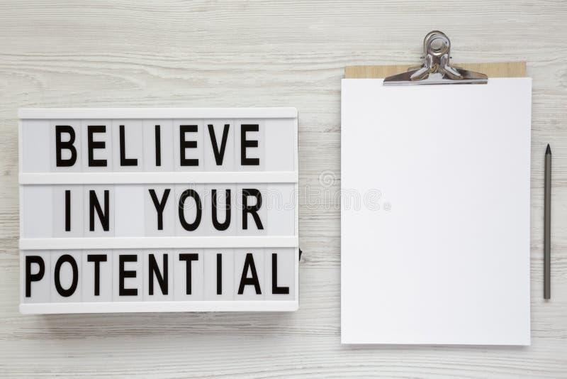 '相信您在一个现代委员会的潜在的'词,有空白的纸片的剪贴板在白色木背景的,顶视图 免版税库存图片