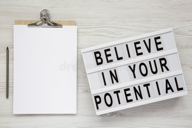 '相信您在lightbox的潜在的'词,有空白的纸片的剪贴板白色木表面上的,顶上的看法 免版税库存图片