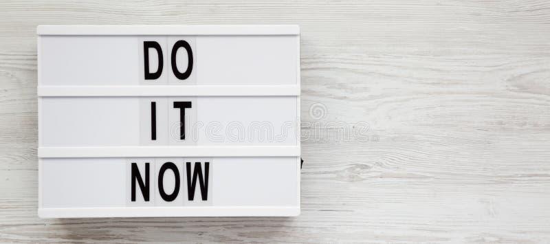 'Ahora hágalo 'las palabras en un tablero moderno en una superficie de madera blanca Endecha plana, visi?n de arriba, superior Es foto de archivo libre de regalías