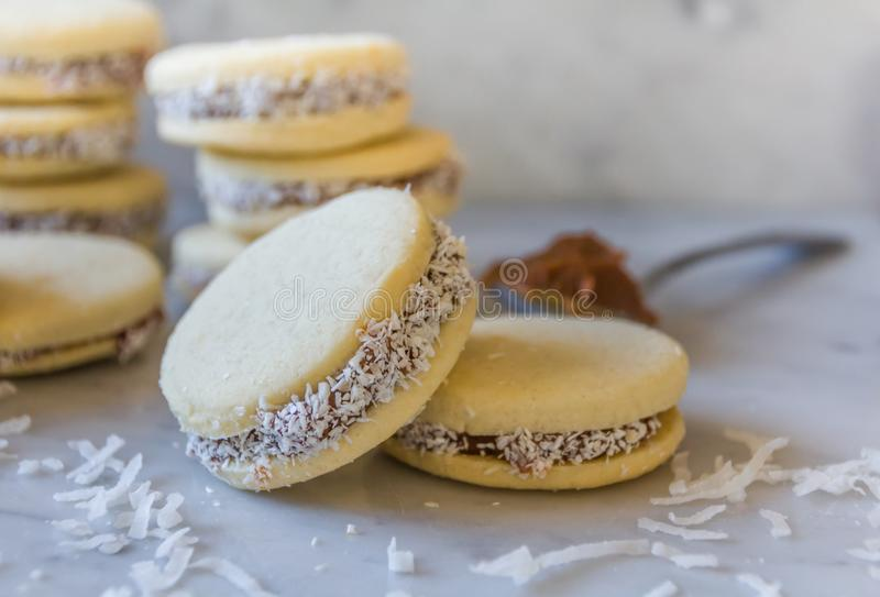 'Alfajores的可口传统阿根廷三明治曲奇饼充满焦糖的牛奶-'dolce de leche'和切细的椰子 免版税库存图片