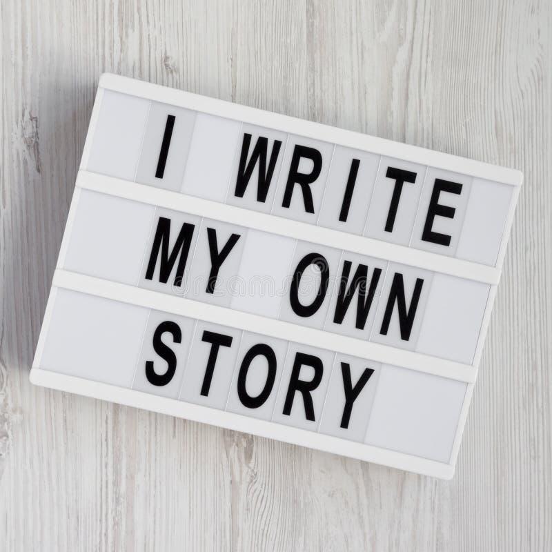 'Escribo las palabras de mi propia historia 'en un lightbox en un fondo de madera blanco Desde arriba, endecha de arriba, plana,  fotografía de archivo