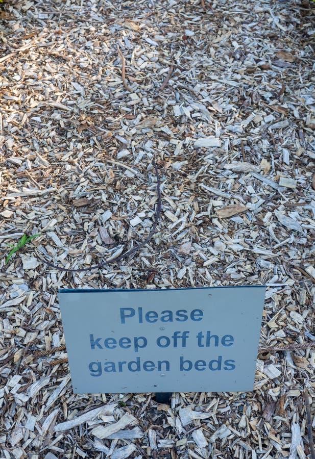 'Evite por favor um sinal de aviso quadrado das camas do jardim em camas de flor vazias no jardim botânico imagens de stock royalty free