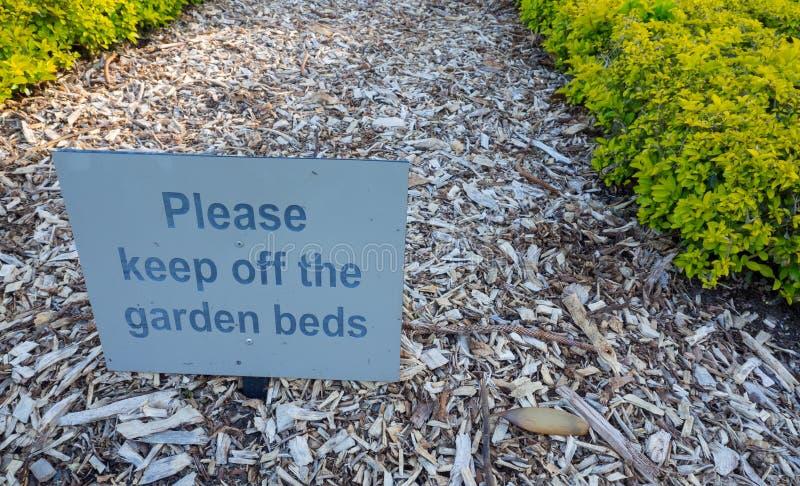 'Evite por favor um sinal de aviso quadrado das camas do jardim em camas de flor vazias no jardim botânico imagem de stock royalty free
