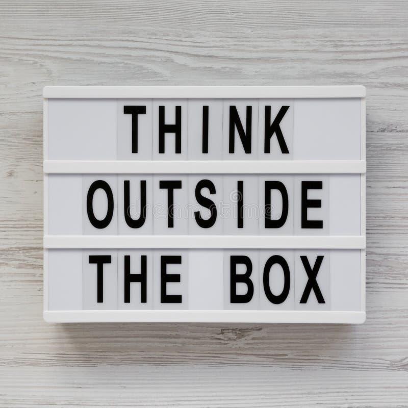 'Pense fora das palavras da caixa em uma placa moderna em um fundo de madeira branco, vista superior Configura??o lisa, a?rea, de imagem de stock royalty free