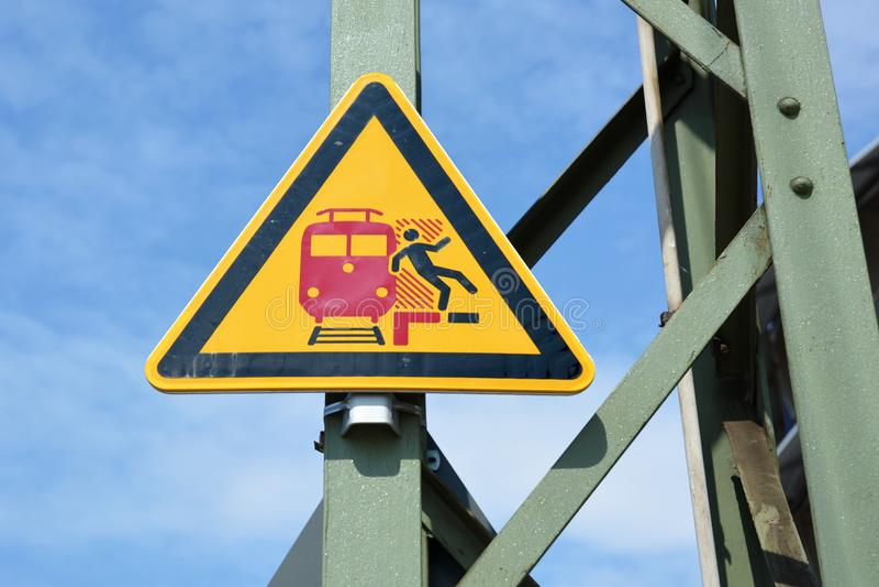 'Geen het stappen over rode lijn 'gele driehoekige waarschuwing signn bij Duits station die gestileerde persoon tonen die van pla royalty-vrije stock foto's