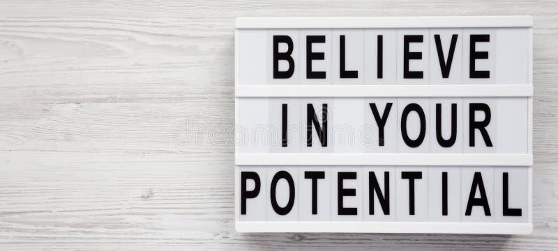 'Geloof in uw potentiële 'woorden op een lightbox op een witte houten oppervlakte, hoogste mening Ruimte voor tekst stock foto's