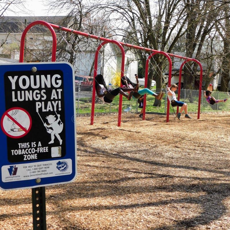 'Junge Lungen am Spiel 'Zeichen auf Spielplatz stockfotos